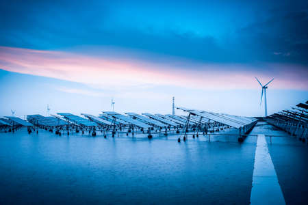 bad weather: solar and wind power in bad weather,green energy background. Stock Photo