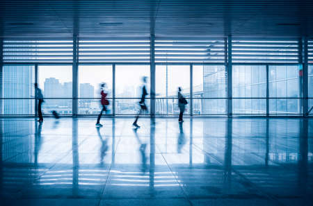 commuters motion blurred with modern corridor in high speed rail station  photo
