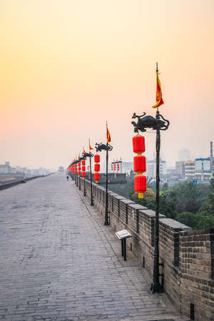 a row of red lanterns on the xian ancient city wall in sunset , China photo