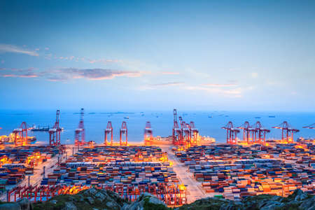 shanghai china: shanghai container terminal in twilight ablaze with lights   Stock Photo
