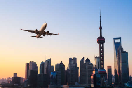 shanghai modern buildings skyline with airplane in sunrise