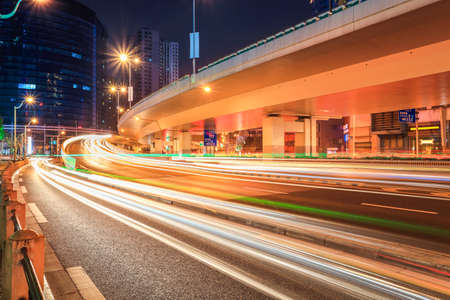 express lane: car light trails on the elevated road at night