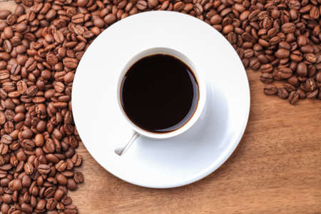brewed: freshly brewed espresso and coffee beans on old wooden table
