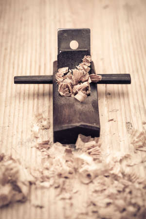 handtool: closeup of the wood planer and woodchips on pine plank background  Stock Photo