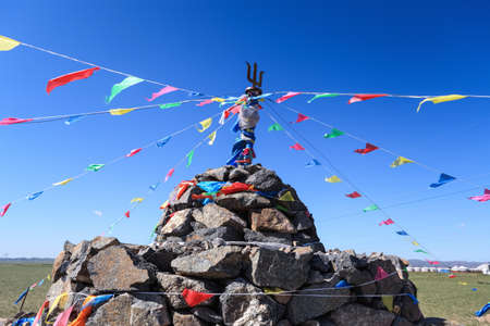 mongolia: closeup of the praying stone and prayer flags on prairie in inner mongolia