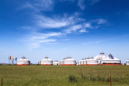 ger: mongolian yurts on the prairie against a blue sky