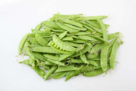 sweet sugar snap: a pile of snow peas on white background