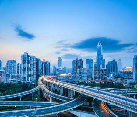 infraestructura: complicada intersección de la carretera con el horizonte de la ciudad moderna en la oscuridad en Shanghai, la infraestructura de transporte por carretera. Foto de archivo