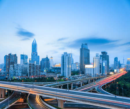 interchange: freeway interchange with modern city skyline in shanghai , road transportation infrastructure.