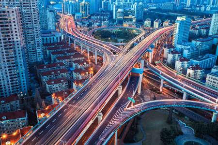 interchange: city interchange bridge closeup with beautiful tail lights in nightfall