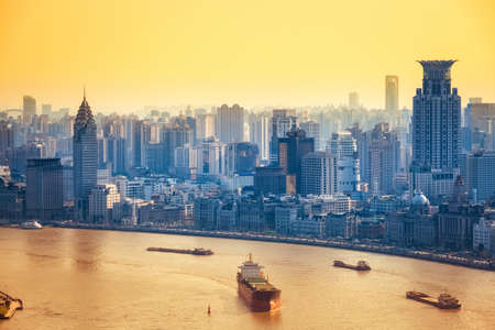freighter: modern city at dusk in shanghai, a bird eye view of huangpu river and the bund