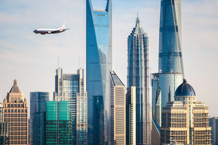 financial world: the modern buildings with airplane in shanghai, China.  Editorial