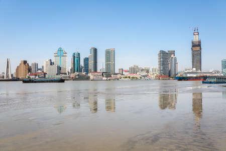 floodplain: shanghai huangpu river and modern building reflection on the beach