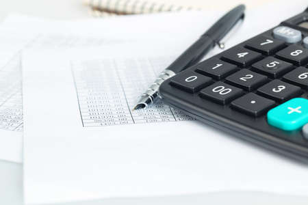 a calculator next to pen and financial documents, abstract accounting concept  photo