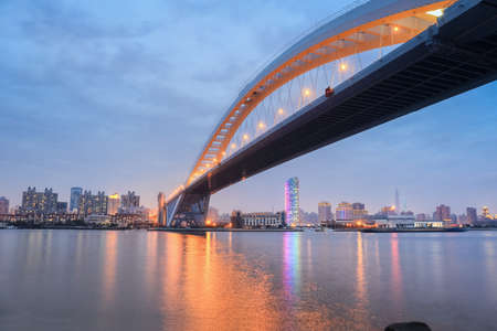 nightfall: lupu bridge in nightfall ,across the huangpu river in shanghai   Stock Photo