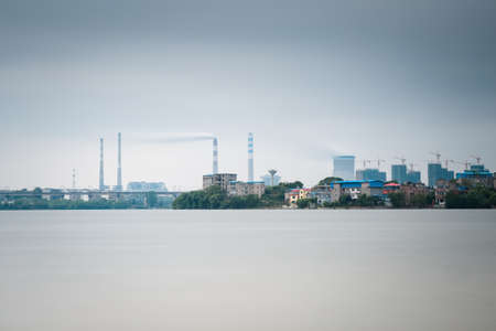 exhalation: thermal power plant with lake ,long exposure time in a cloudy sky