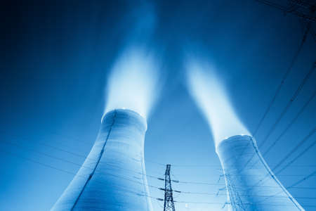 nuclear plant: upward view of the cooling towers in a power plant at night  Stock Photo