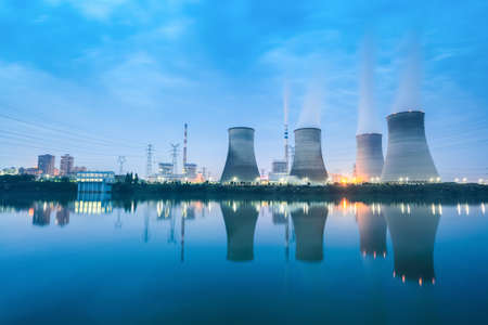 nightfall: thermal power plant in nightfall ,cooling towers and reflection in the river