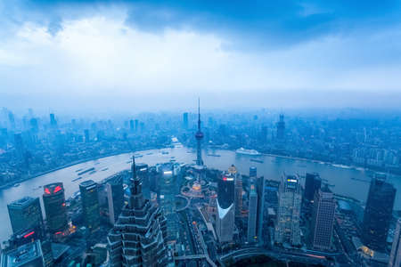 financial world: a birds eye view of shanghai at dusk with cloudy sky