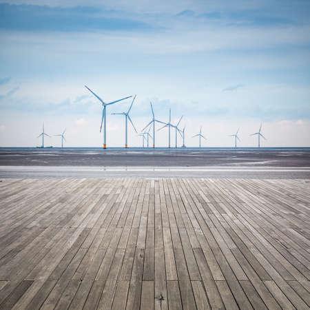 木製の床と干潟、風力発電所 写真素材