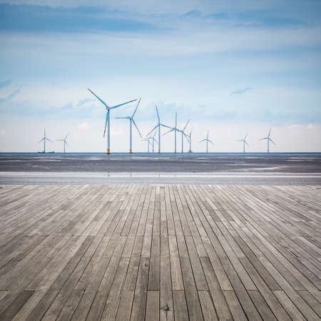 sustainable tourism: wind farm in mud flat with wooden floor