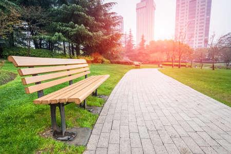 banc de parc: parc de la ville après la pluie, banc et le chemin de piétonne Banque d'images