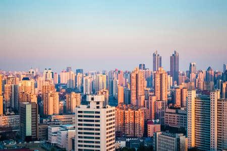 población: ciudad moderna en la oscuridad en Shanghai, bajo el ángulo de la luz del sol brilla en los edificios de los bosques urbanos. Foto de archivo