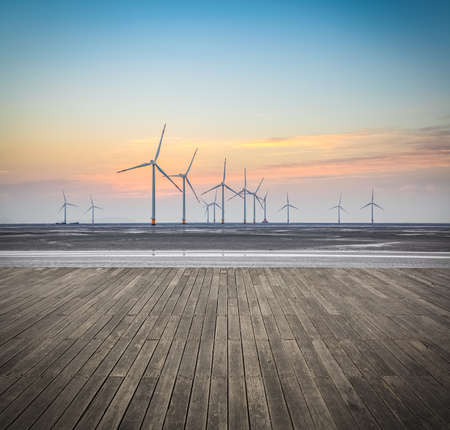 offshore wind farms in sunrise with wooden floor , renewable energy background. Archivio Fotografico