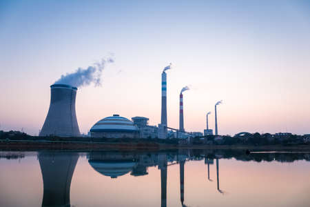 exhalation: power plant at twilight and the reflection of the lake Editorial