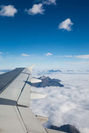 wing of an airplane flying above the clouds and mountains photo