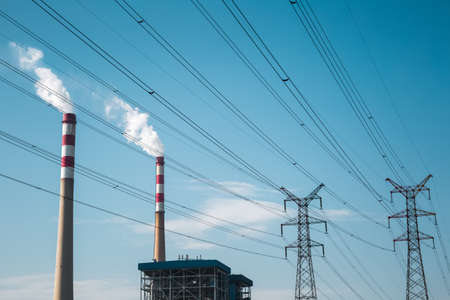 smoke stack: power plant chimney and high voltage transmission pylon with blue sky