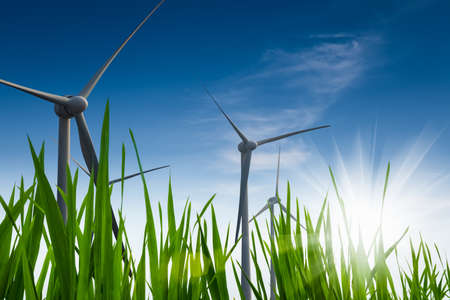 green energy background ,  wind power with green grass against a blue sky Foto de archivo
