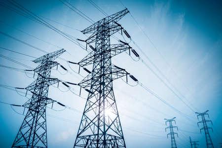 torres de alta tension: transmisión de electricidad pilón recortaba contra el cielo azul al atardecer Foto de archivo