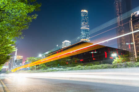light trails on the city road with futuristic city in guangzhou central business district photo