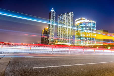 beautiful light trails of city traffic on modern residential building background at night photo