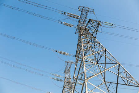 over voltage: high voltage towers over blue sky , upward view Stock Photo