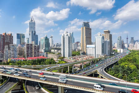 highway interchange: shanghai highway overpass with modern city skyline against sunny sky , China