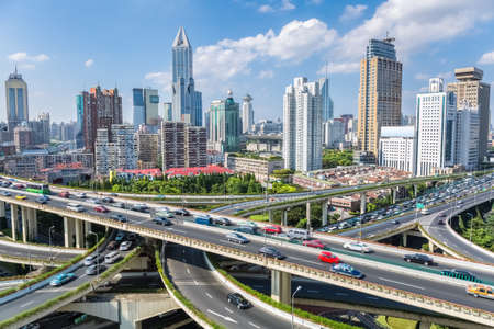 aerial: shanghai highway overpass with modern city skyline against sunny sky Stock Photo