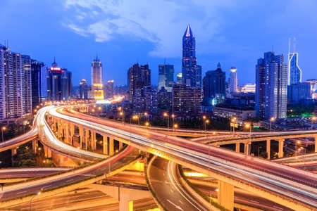 flyover: shanghai highway overpass with modern city skyline in nightfall