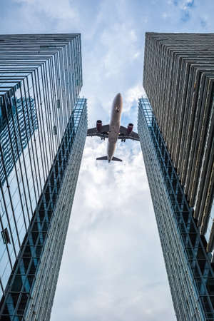 corporate travel: upward view of the airplane between the two glass skyscrapers