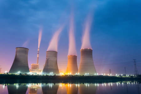 nuclear power station: power plant at night , cooling tower closeup with steam Editorial