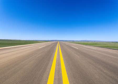 wide road in prairie against a blue sky