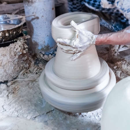 out of production: making of porcelain on wheel,kaolin on jolley ,a process with the porcelain production, through the power of the rotation, use both hands to pull out the shape of the porcelain. Stock Photo