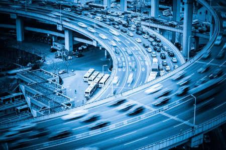 aerial: pesada primer tráfico, los vehículos de movimiento borroso en viaducto con tono azul