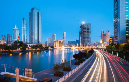 modern buildings and city traffic on both sides of the Haihe river in Tianjin at night