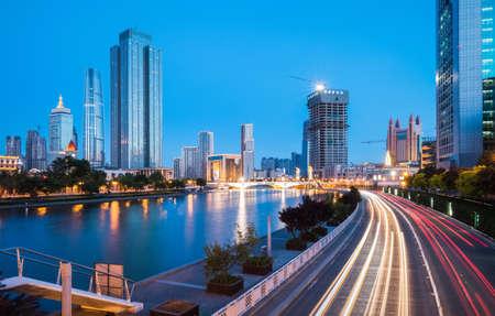 desarrollo económico: modernos edificios y tráfico de la ciudad a ambos lados del río Haihe en Tianjin en la noche