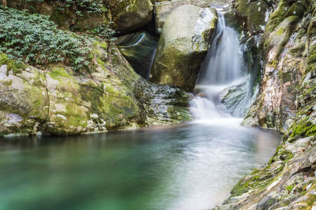 small waterfall with deep pool of  clear water in lushan, China
