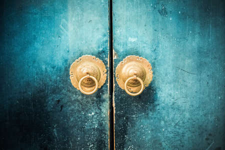 old wooden door and antique oriental knocker Фото со стока