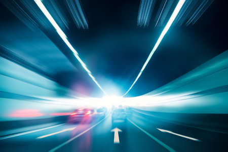light speed: highway tunnel exit to light with speeding car motion blur