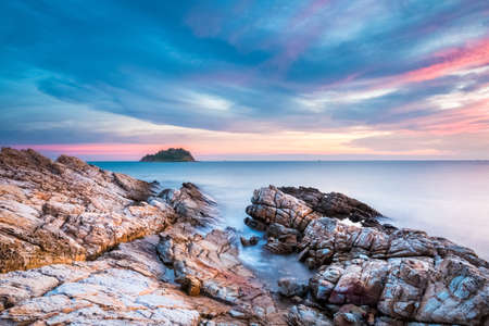 koh samet: beautiful dusk over the sea with rocks and sunset glow in koh samet island,thailand. Stock Photo